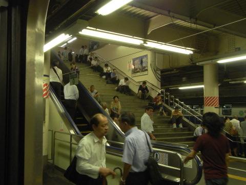 台風接近で電車の止まった上野駅の階段に座り込む人々