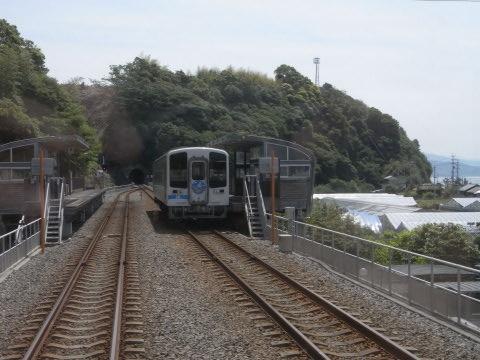行く先のトンネルの上の山に崖崩れの跡の残る穴内駅に停まるごめん・なはり線の列車