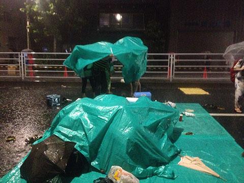 隅田川花火大会の途中で降り始めた雷雨にビニールシートをかぶって雨を凌ぐ人